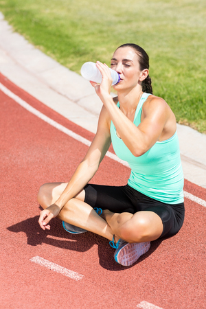 tomando refresco: Tired female athlete sitting on the running track and drinking water on a sunny day