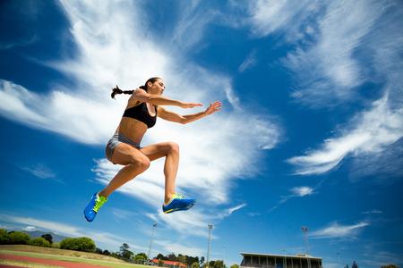 salto de longitud: Atleta femenina realizar un salto de longitud durante una competición Foto de archivo