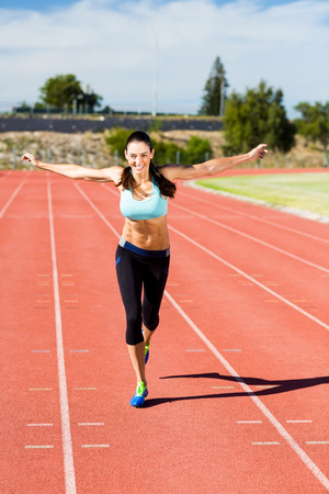 outstretched: Portrait of happy female athlete running with arms outstretched