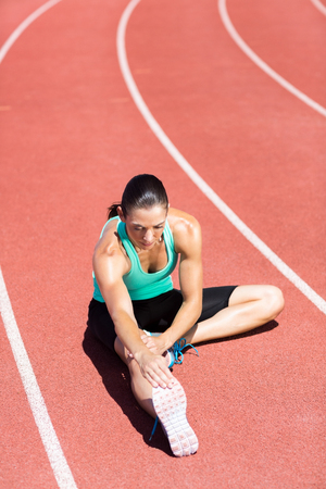 hamstring: Female athlete stretching her hamstring on running track Stock Photo