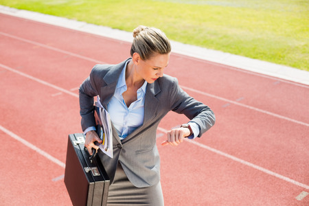 career timing: Businesswoman with briefcase in ready to run position on running track Stock Photo