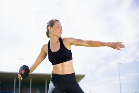 discus: Female athlete about to throw a discus in stadium