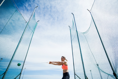 hammer throw: Female athlete performing a hammer throw in stadium Stock Photo