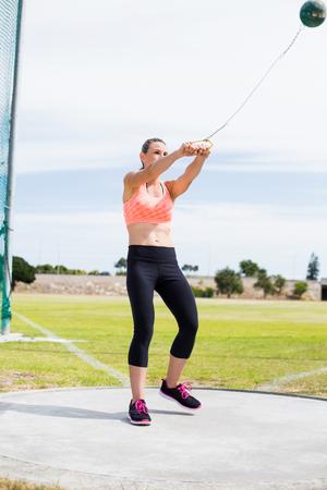 hammer throw: Female athlete performing a hammer throw in stadium Stock Photo