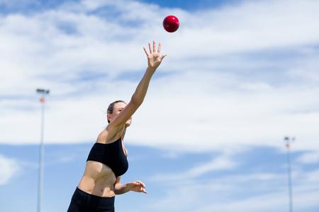 lanzamiento de bala: Confident female athlete throwing shot put ball in stadium