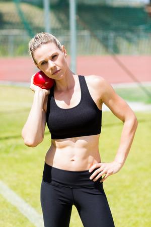 lanzamiento de bala: Retrato de la mujer atleta que se prepara para lanzar bola de tiro puesto en estadio