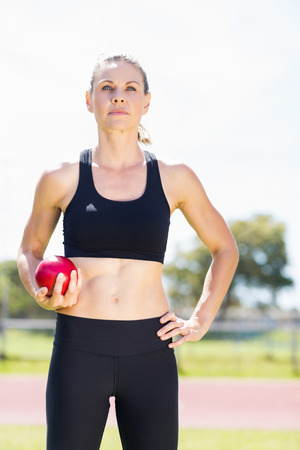 lanzamiento de bala: Atleta de sexo femenino confidente que sostiene una bola de lanzamiento de peso en el estadio