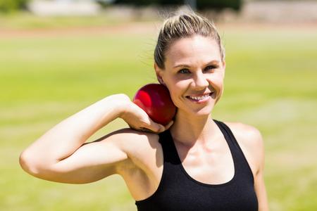 lanzamiento de bala: Retrato de la mujer atleta feliz que se prepara para lanzar bola de tiro puesto en estadio