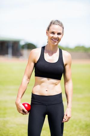 lanzamiento de bala: Retrato de la mujer atleta feliz que sostiene una bola de lanzamiento de peso en el estadio