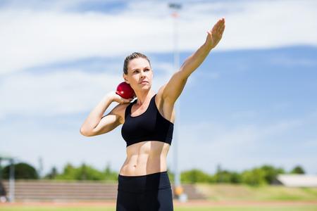 lanzamiento de bala: Atleta de sexo femenino confidente que se prepara para lanzar bola de tiro puesto en estadio Foto de archivo