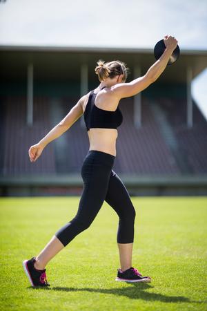 lanzamiento de disco: De la mujer atleta a punto de lanzar un disco en el estadio
