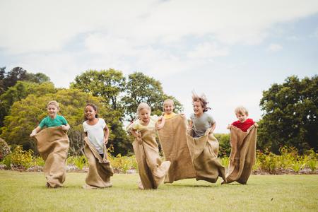Kinderen met een zak race in het park op een zonnige dag