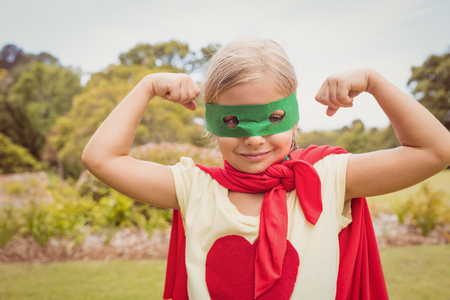 contracting: Little girl wearing superhero costume contracting biceps in the park