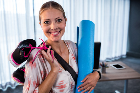 office shoes: Casual businesswoman with yoga mat and sports shoes in the office Stock Photo