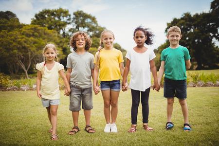 amabilidad: Los niños tomados de la mano en el parque Foto de archivo
