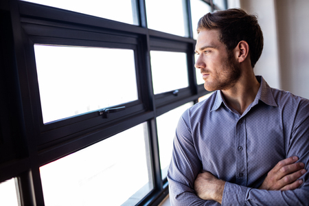 looking out: Businessman with arms crossed looking out of the window Stock Photo