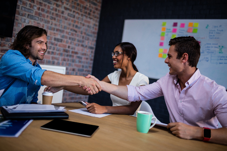 interacting: Group of hipster interacting and handshaking in the office Stock Photo