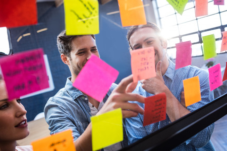 Hipsters het lezen van een post-it op een venster in het kantoor