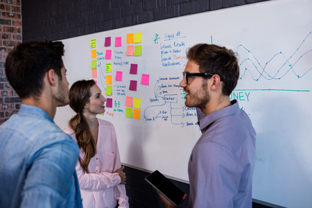 Coworkers interacting front of a board in the office
