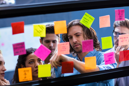 Hipsters reading a post it on a window in the office