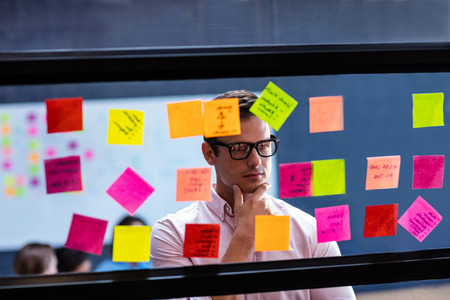 Hipster reading a post it on a window in the office
