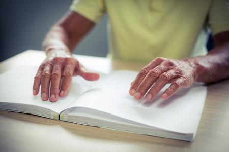 braile: Hombre mayor ciego que lee un libro en braille en el hogar Foto de archivo