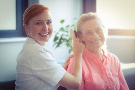 combing hair: Female nurse combing hair of senior woman at home