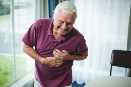 dolor de pecho: Hombre mayor que sufre de dolor en el pecho en casa Foto de archivo