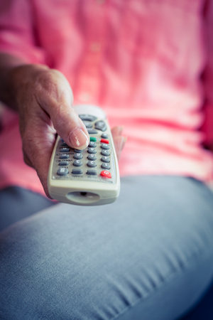 changing channel: Senior woman changing tv channel at home Stock Photo