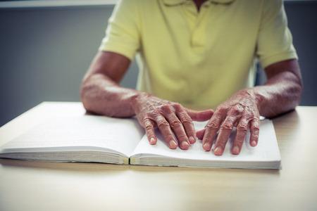 braille: Hombre mayor ciego que lee un libro en braille en el hogar Foto de archivo