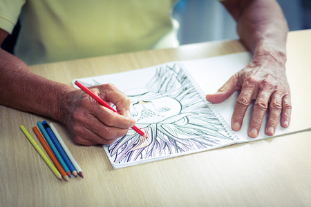 colored pencil: Senior man drawing with a colored pencil in drawing book at home