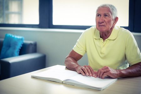 braille: Senior blind man reading a braille book at home Stock Photo