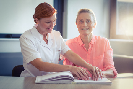 Female nurse helping patient in reading the braille book at home