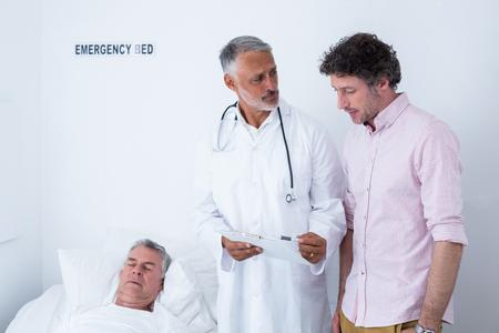 emergencia medica: Doctor de sexo masculino la discusión de informe médico con el hombre en el hospital Foto de archivo