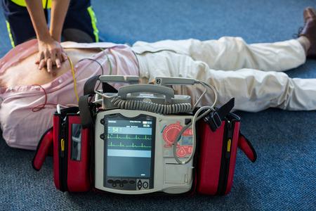 Paramedic using an external defibrillator during cardiopulmonary resuscitation in hospital Stock Photo