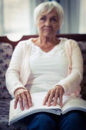 braile: mujer ciega que lee un libro en braille en el hogar