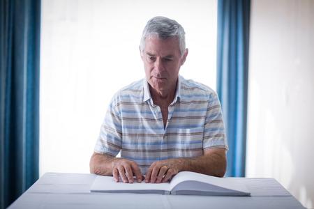 braille: ciego que lee un libro en braille en el hogar Foto de archivo