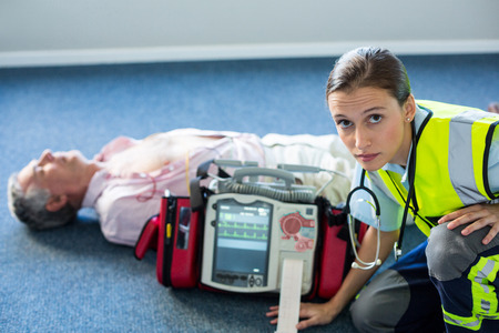resuscitation: Paramedic using an external defibrillator during cardiopulmonary resuscitation in hospital Stock Photo