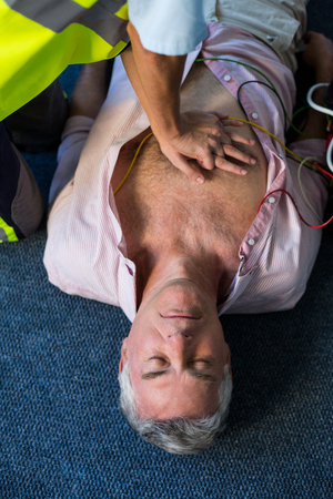 Cardiac Arrest: Paramedic using an external defibrillator during cardiopulmonary resuscitation in hospital Stock Photo