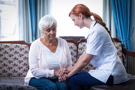 consoling: Female doctor consoling senior woman in living room at home Stock Photo