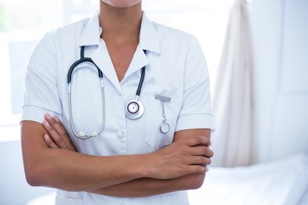 midsection: Mid-section of female doctor standing with arms crossed in hospital