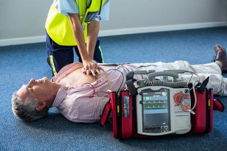 cardiopulmonary resuscitation: Paramedic using an external defibrillator during cardiopulmonary resuscitation in hospital Stock Photo