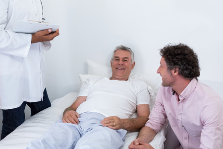 hospital patient: Man sitting next to patient in hospital