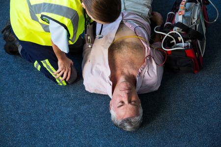 Paramedic using an external defibrillator during cardiopulmonary resuscitation in hospital Stock Photo