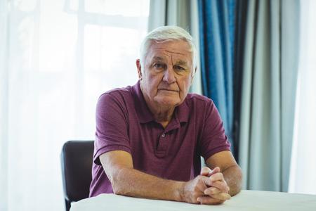 beside table: Portrait of worried senior man sitting beside table