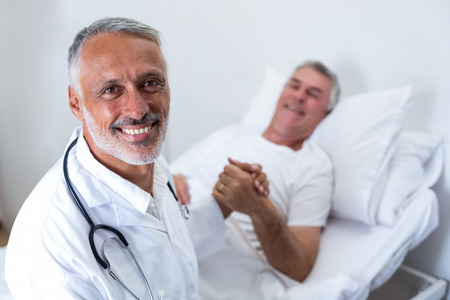 consoling: Male doctor consoling senior man in hospital