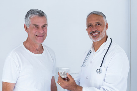 doctor giving pills: Portrait of male doctor giving pills to senior man in hospital