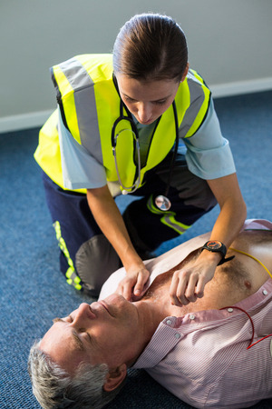 chest compression: Paramedic using an external defibrillator during cardiopulmonary resuscitation in hospital Stock Photo