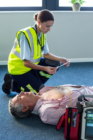 arrest women: Paramedic using an external defibrillator during cardiopulmonary resuscitation in hospital Stock Photo