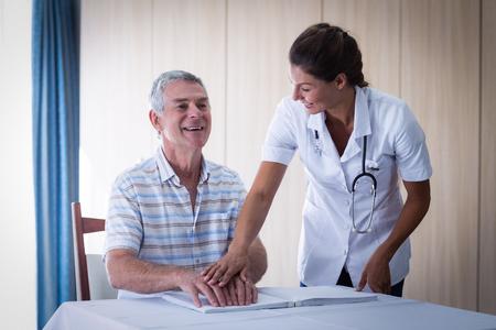gente adulta: médico femenino que ayuda a los pacientes en la lectura del libro en braille en el hogar